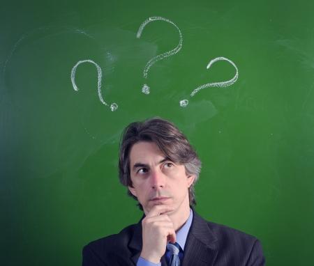 Een man met een uitdrukking van vragen en vraagtekens over hun hoofden