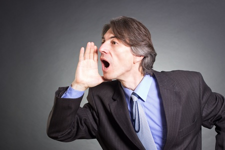 gestos de la cara: Empresario gritando con las manos juntas como un megáfono.
