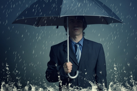 special service agent: Businessman with an umbrella in the rain  Stock Photo