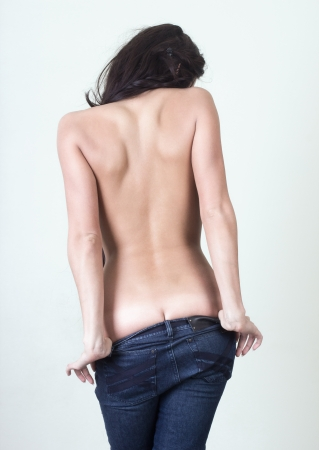 nude back: Nude young woman in jeans.