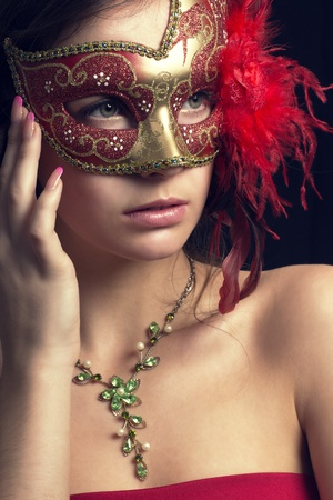 beautiful young woman in a mysterious venetian mask photo