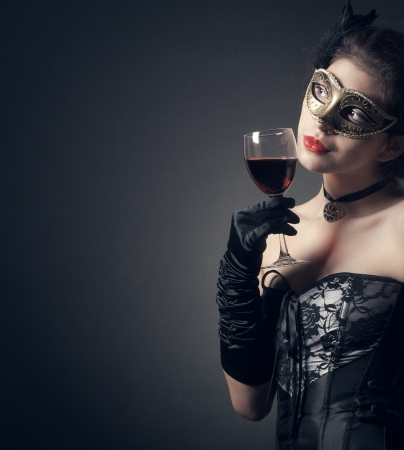 woman in carnival mask and a glass of red wine. photo