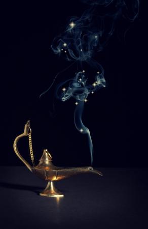 genie in a bottle: aladdin magic lamp on black with smoke