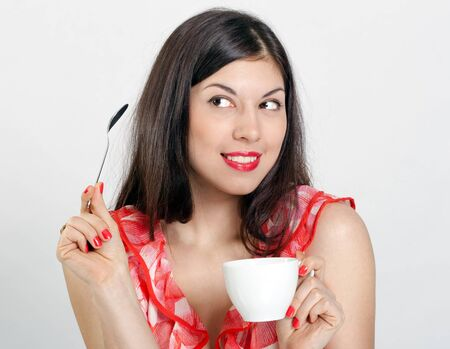 Cheerful young woman with a cup of coffee on a white background. photo