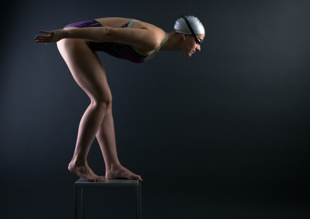 swimmer: Woman swimmer prepared to jump into the water.
