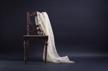 Vintage chair draped with a dark background. photo
