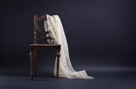 Vintage stoel gedrapeerd met een donkere achtergrond. Stockfoto