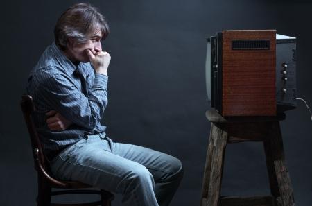 spectator: Man watching TV.