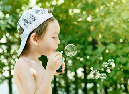 Little boy blowing soap bubbles photo