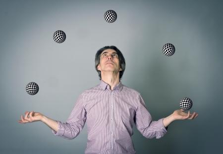 Een man jongleren verscheidene ballen