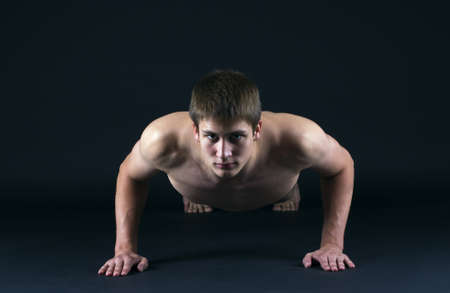 Man doing push ups isolated on black  photo