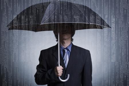 Businessman with an umbrella under digital rain  photo