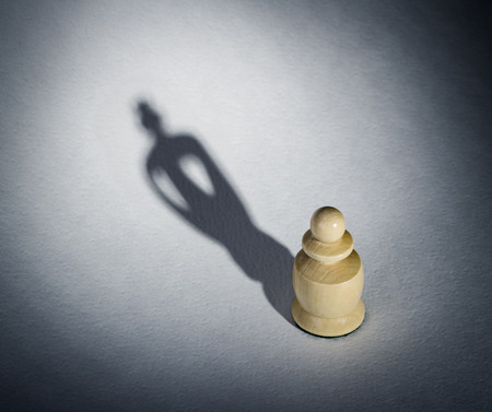 A chess pawn casting a king piece shadow - strength and aspirations concept photo