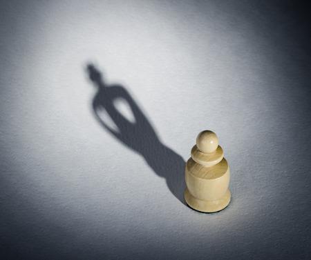 pensamiento estrategico: Un peón de ajedrez echando un rey pieza sombra - Concepto de fuerza y ??aspiraciones