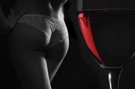Belle silhouette d'un corps de femme et un verre de vin rouge sur un fond noir