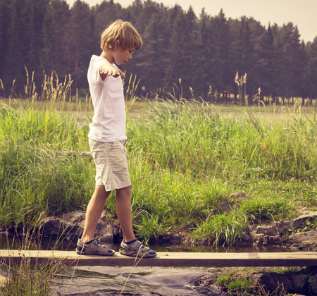 Boy on a wooden bridge photo
