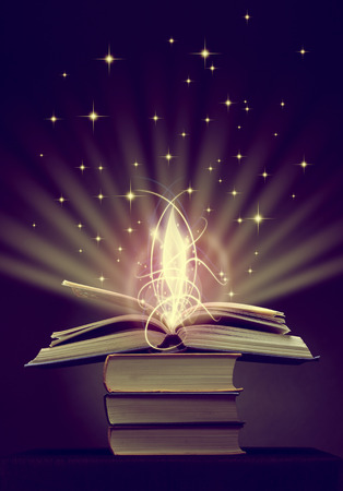 opened magic book with magic lights