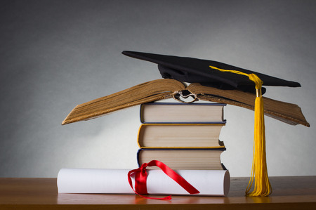 A mortarboard and graduation scroll, tied with red ribbon, on a stack of old battered book