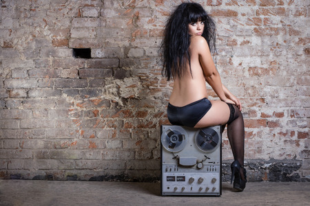 Sexy nude woman sitting on retro tape against the brick wall. photo