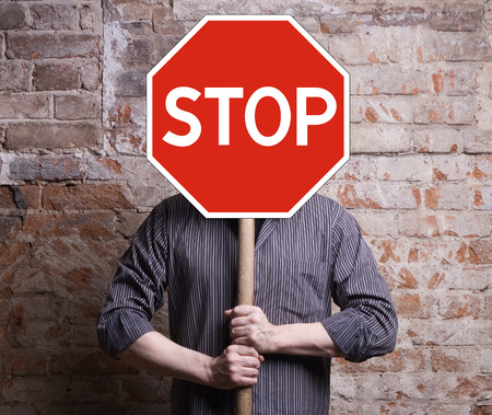 prohibition signs: A man holds a sign forbidding face. Stock Photo