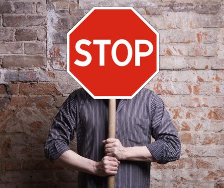 se�ales de peligro: Un hombre sostiene un cartel que proh�be la cara.