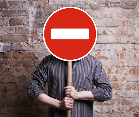 forbidding: A man holds a sign forbidding face. Stock Photo