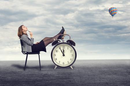 sen: Mladá podnikatelka snění sedí na židli pod širým nebem.