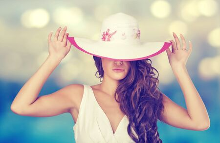 Elegant woman in a white hat on the beach. photo