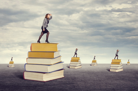 Businesswoman looking into the distance while standing on the foot of books. photo