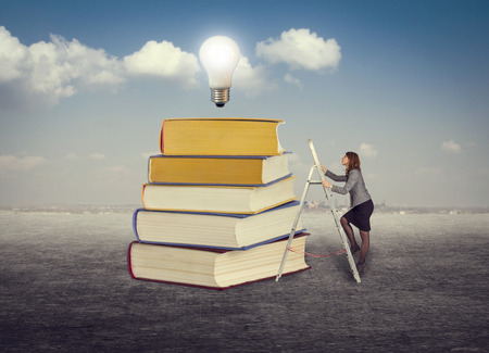 Businesswoman climbing the stairs to the foot of books for new ideas. photo