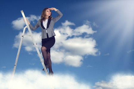 Businesswoman climbing the stairs to the sky looking into the distance. photo