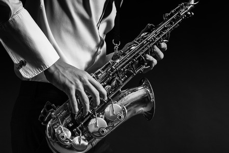 A man plays the saxophone close up.