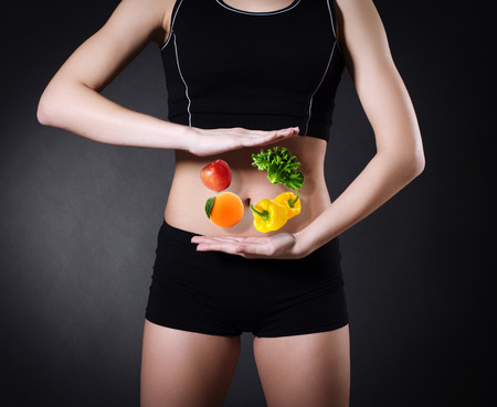 parsley digestion: Healthy eating. Vegetables and fruits on a background of a female belly closeup.