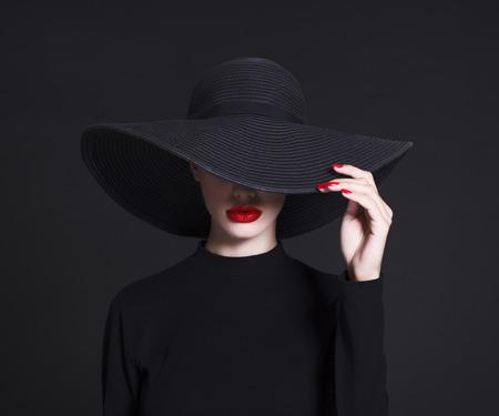 Donna di lusso in un grande cappello nero e le labbra luminose su sfondo nero Archivio Fotografico - 66724756