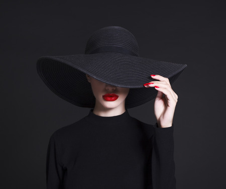 Luxury woman in a large black hat and bright lips on black background Reklamní fotografie - 66724756