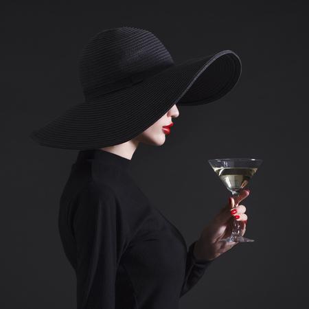 Luxe vrouw in een grote zwarte hoed en heldere lippen met een glas Martini. Stockfoto