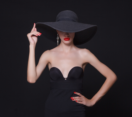black hat: Luxury woman in a large black hat and bright lips on black background