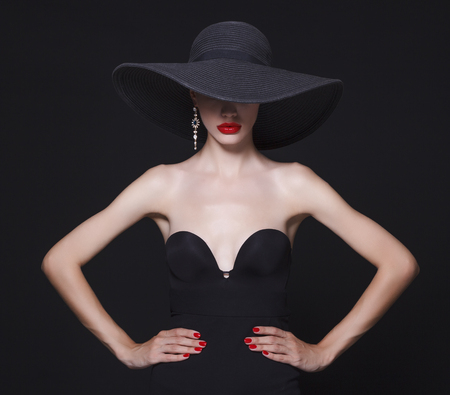 white hat: Luxury woman in a large black hat and bright lips on black background