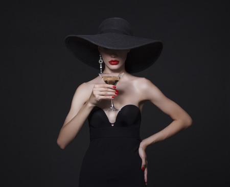 大きな黒い帽子とマティーニのグラスの明るい唇の高級女性。 写真素材