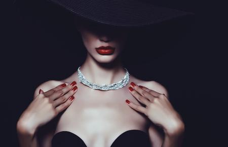 Un collar de diamantes en el cuello de una mujer de lujo en un sombrero. Foto de archivo - 70769048