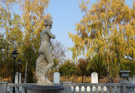 Statue of Venus on the background of yellow birch trees in the park of Aseev manor, Tambov, Russia