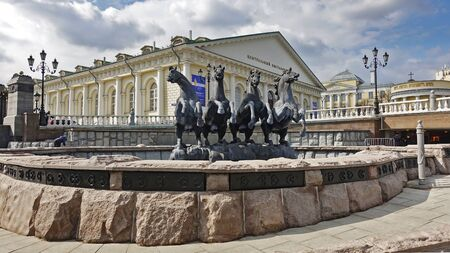 Moscow, Russia. April 14, 2019 Fountain Four Seasons on Manezhnaya Squares and the building of the central exhibition hall. Text translation: central exhibition hall