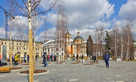 Moscow, Russia. April 14, 2019. Walking people in Zaryadye Park in spring, view of the Church of St. Barbara. TEXT TRANSLATION: Gostiny Dvor