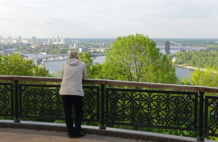 A man leaning on the railing of the fence, admiring the view of Kiev and the Dnieper on Vladimirskaya Gorka