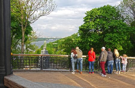 Kiev. Ukraine. May 16, 2019 Spring evening in Kiev on the Vladimir hill. A group of people over the Dnipro admire the Baptist Редакционное