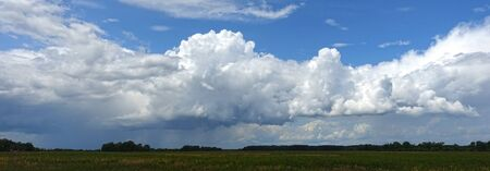 A huge white rain cloud hanging over a field