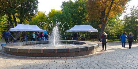 Kiev Ukraine October 01 2019 Autumn sunny day in Shevchenko park. Rest of people at the fountain Редакционное