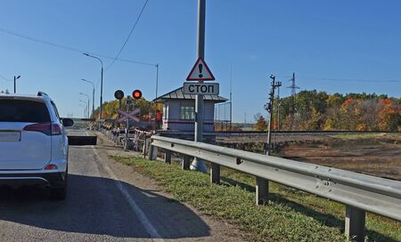 Red light of a traffic light at a railway crossing. Autumn day, Russia. Text Translation: Stop