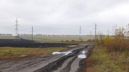 Rural dirt road going through fields after rain on an autumn day