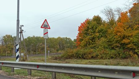 Road sign on the highway in Russia, warning about the railway tracks. Autumn day Banco de Imagens
